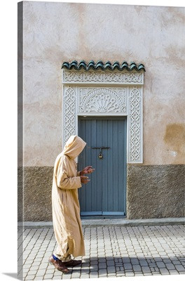 A man wearing a djellaba walks past a decorative doorway in the medina (old town)