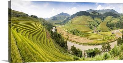A river flows through lush, green rice terraces, Mu Cang Chai, Yen Bai Province, Vietnam