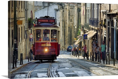 A tramway in Alfama district with the Motherchurch in the background. Lisbon, Portugal