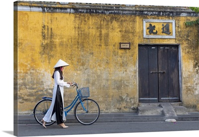 A Vietnamese Girl Cycles Past A Colonial Building In Hoi An Ancient Town, Vietnam