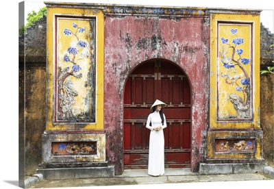 A Vietnamese Girl Stands In Front Of Historical Gate In Hue Imperial Citadel, Vietnam