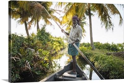 Boatman guiding the vessel through Keralan backwaters near North Paravoor, Kerala, India