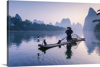 China, Guanxi, Yangshuo. Old chinese fisherman on the Li river, fishing with cormorants