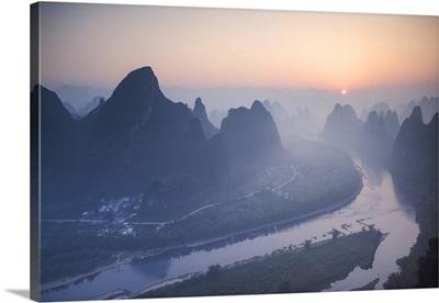 China, Guanxi, Yangshuo. Sunrise over Li river and karst peaks, elevated view