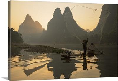 Cormorant fisherman throwing net on Li River at dawn, Xingping, Yangshuo, Guangxi, China