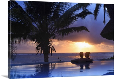 Couple relaxing inside infinity pool overlooking the beach at luxurious resort