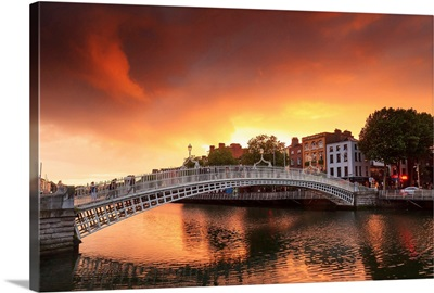 Europe, Dublin, Ireland, people crossing Halfpenny bridge on the Liffey river at sunset