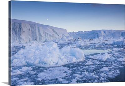 Greenland, Disko Bay, Ilulissat, floating ice at sunset with moonrise