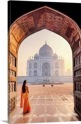 India, A Beautiful Woman In A Red And Yellow Sari In Front Of The Taj Mahal At Sunrise