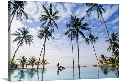 Indonesia, Bali, A Young Woman Sitting On The Edge Of A Swimming Pool Under Palm Trees