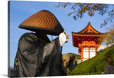 Japan, Honshu, Shinto Priest seeking donations wearing a Bamboo hat
