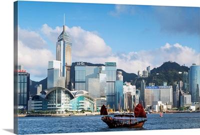 Junk boat passing Convention Centre and Hong Kong Island skyline, Hong Kong, China