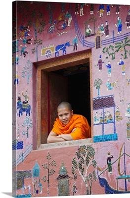 Laos, Luang Prabang, Monk at Window of the Reclining Buddha Sanctuary
