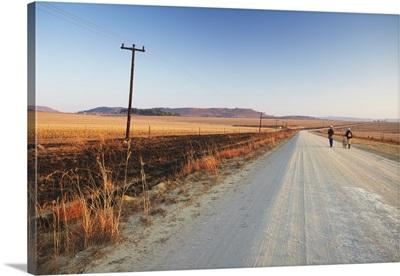 Men walking on dirt road at dawn, Winterton, KwaZulu-Natal, South Africa