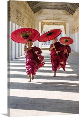 Myanmar, Mandalay division, Bagan. Three novice monks running with red umbrellas