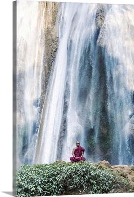 Myanmar, Pyin Oo Lwin. Burmese monk meditating under Dattawgyaik Waterfall