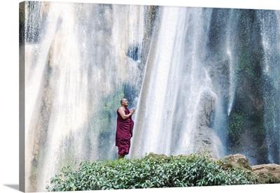 Myanmar, Pyin Oo Lwin. Burmese monk praying under Dattawgyaik Waterfall