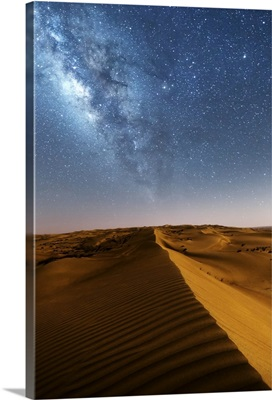 Oman, Wahiba Sands. The sand dunes at night lit by the moon with the milky way