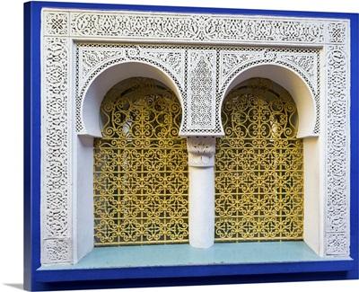 Ornate window against blue wall at Jardin Majorelle gardens