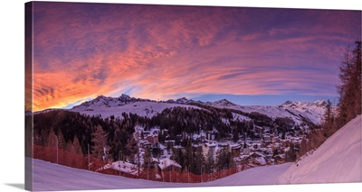 Panorama of the alpine village of Madesimo and snowy ski slopes at sunset