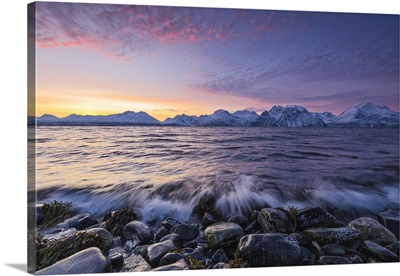 The waves breaking on the stones beach during sunset. Norway, Lapland, Europe