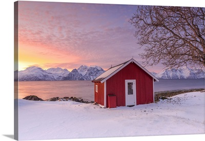 Traditional Norwegian house during a sunset on the fjord.