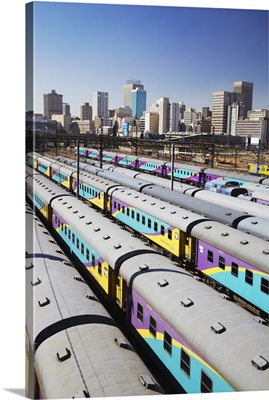 Train carriages at Park Station with city skyline, Johannesburg, South Africa
