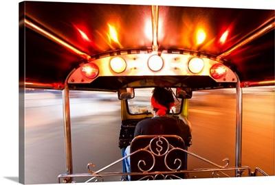 Tuk Tuk or auto rickshaw in motion at night, Bangkok, Thailand