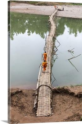 Two buddhist monks walk across bamboo bridge, Luang Prabang, Laos