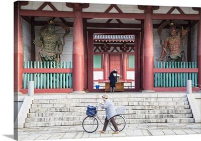 Woman pushing bicycle past Shitenno-ji temple, Tennoji, Osaka, Kansai, Japan