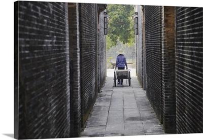 Woman with wheelbarrow in alleyway in Majiang Long village Kaiping, Guangdong, China