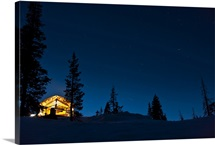 Lit cabin in mountains surrounded by snow and dark sky, Donner, California
