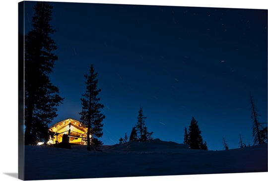 Lit A Donner lit cabin in mountains surroundedsnow and dark sky, donner