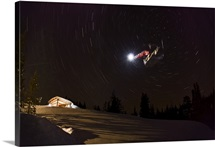 Snowboarder making jump in the night with radial star shot, Donner, California