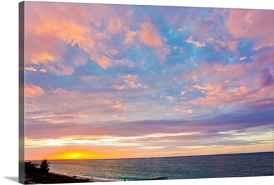 A beautiful delicate pink and purple sky at sunset over Grace Bay, and the shore