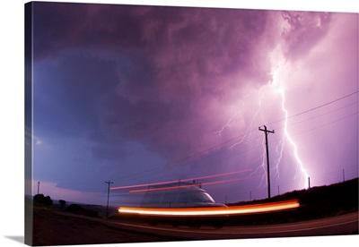 A large lightning bolt strikes behind a storm chaser's moving van