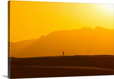 A lone man walks on top of sand dunes during sunset