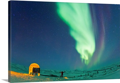 A man looks in awe at the aurora borealis in the Arctic Circle
