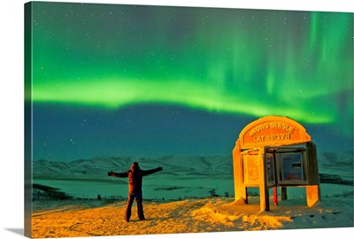 A man looks in awe at the northern lights near the Arctic Circle sign