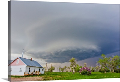 A rotating mesocyclone supercell thunderstorm filling the sky over a small church