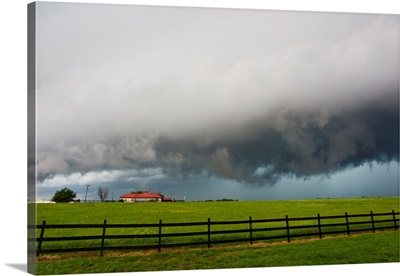 A supercell thunderstorm darkens the sky over a ranch and fields