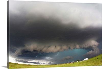 A thunderstorm with dark skies and illuminated a blue rain/hail shaft
