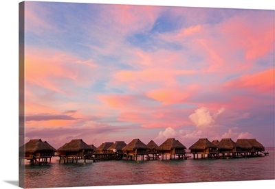 A vibrant pink and red sunset over bungalows on stilts over the water