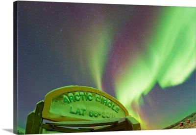 An aurora borealis at the famous Arctic Circle sign