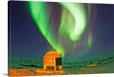 An aurora borealis near the famous Arctic Circle sign