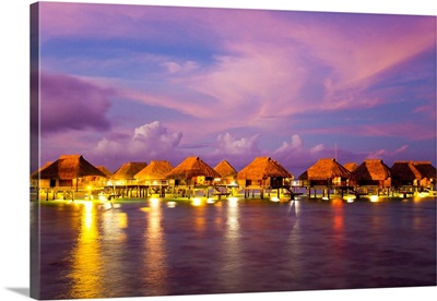 Over-water bungalows on stilts lit up under a pink and purple sky at dusk