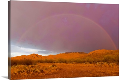 Rainbow and purple sky on the backside of thunderstorm in a desert