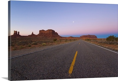 Rock formations and moon at dawn on the way to Monument Valley