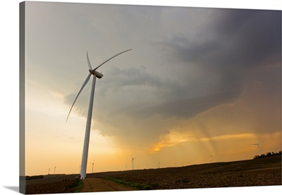 Windmills or turbines that produce kinetic energy lined up on farms