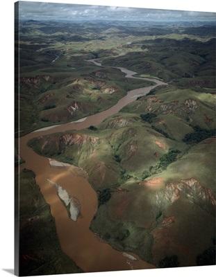 Deforested and deeply eroded hills alongside silted river, Betsiboka River, Madagascar